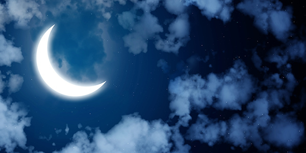 A crescent moon in a cloudy night sky.