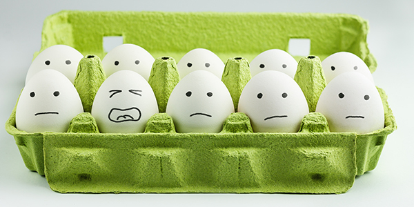 A carton of eggs with faces drawn on them. 11 look neutral while one looks like it's stressed.