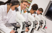 Image of four doctors in lab coats looking through microscopes