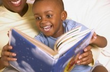 image of an adult reading to a happy child