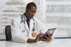image of a doctor looking at a tablet