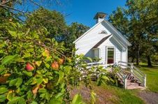 Image of a small church with an apple tree in the foreground