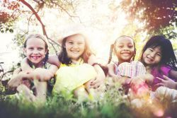 photo of four children lying in the grass