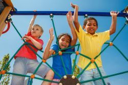 three kids playing on playground equipment