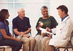 photo of a doctor speaking with three patients. all are seated.