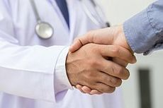 photo of two people shaking hands, one has a stethoscope around their neck