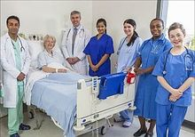 photo of six doctors standing next to a hospital patient