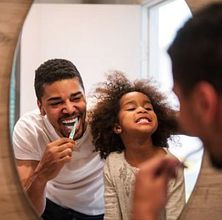 photo of a dad and daughter brushing their teeth and laughing in the mirror