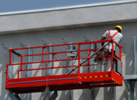 photo of a construction worker on a lift working on the outside of a building