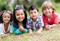 photo of four children laying in the grass