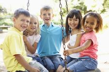 photograph of five children on playground equipment