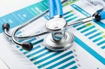 photo of a stethoscope lying on top of data charts