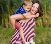 photo of a pregnant woman giving her son a piggy-back ride