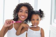 photo of a woman and her daughter brushing their teeth