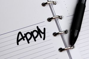 a pen lying on a piece of paper with the word 'apply' written on it