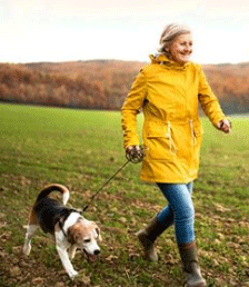 photo of an older american woman walking her dog