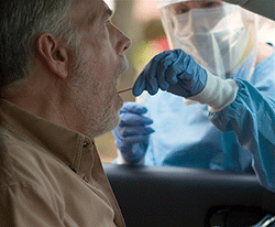 photo of a man getting swabbed while sitting  in his car by a health care worker