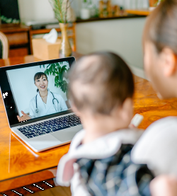 photo of a mom and child on a telehealth call with a doctor