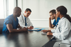 photo of four health care workers having a discussion