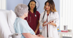 photo of a woman in the hospital talking with two health care workers
