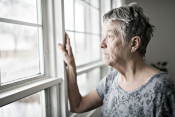 photo of an elderly woman looking out a window.
