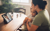 photo of a woman and her child on a telehealth call with a physician