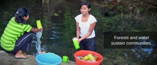 Two smiling women collect water from a stream in sports bottles.