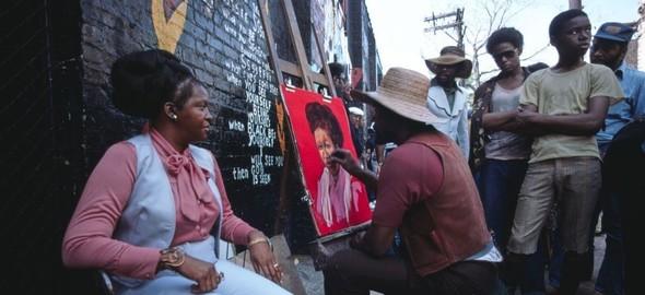 A street artist paints a portrait of a Black woman