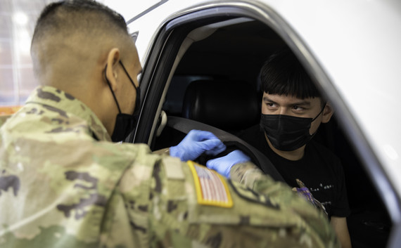Service member gives COVID-19 vaccine to child in car