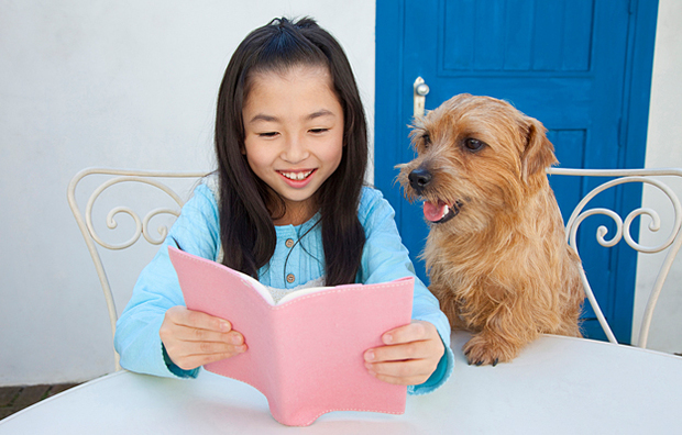A young girl reading to her dog.