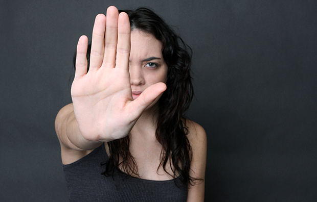 A teenage girl holding out her hand signalling to stop.