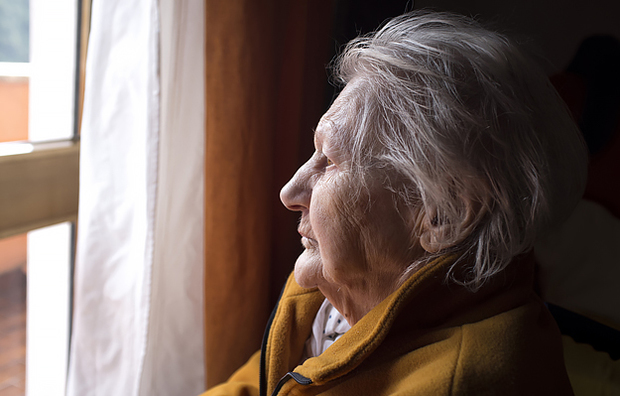 An elderly woman looking out a window.