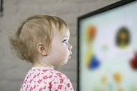 Photo of young child looking at computer screen, associated with January 2019 research spotlight article on computer-detected postural changes in children with autism.