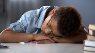 Photo of young male boy resting head on desk, associated with March 2019 research spotlight article on physiological indicators for personalized medicine: towards optimal behavioral interventions for at-risk children.