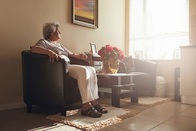 Photo of older woman sitting on chair looking out the window, associated with April 2019 research spotlight article on social isolation - associations with physical activity and sedentary behavior.