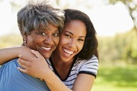 Graphic of an older and younger African-American female hugging and smiling, associated with June 2019 research spotlight article on Researchers make strides in treating depression in Parkinson's Disease.