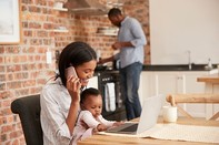 Family of three, man standing above the stove and woman talking on phone with child sitting on her lap using a laptop computer, associated with August 2019 research spotlight article on Stress during pregnancy is linked with long-term effects on mother's health.