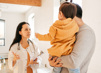 Father and toddler consulting with doctor