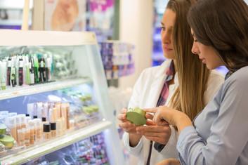 Shop assistant helping customer choose cosmetics