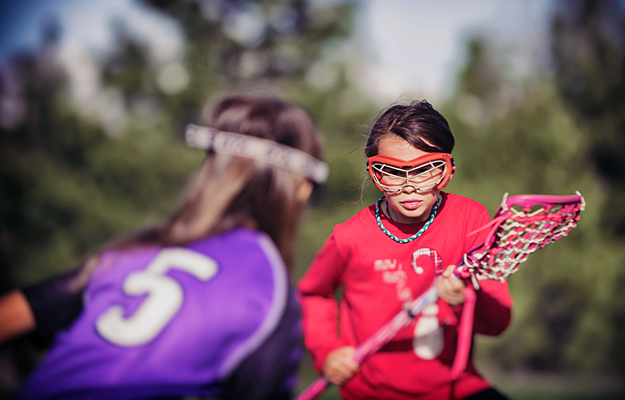 Two young girls playing lacrosse and wearing protective eyewear.