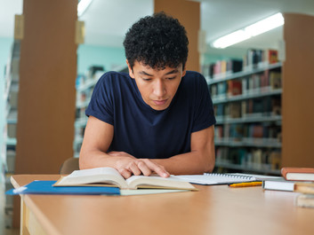 Student studying a book in the library
