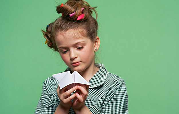 """A young girl holding a paper stress catcher """"fortune teller""""."""