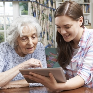older woman on computer with younger woman