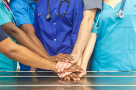 Multiracial team of doctors placing hands on top of each other