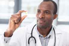 Stock photo of Black physician examining a pill