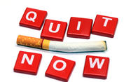 """Stock image of used cigarette in between message stating """"Quit now"""""""