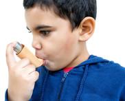 Hispanic boy holding inhaler to his mouth