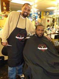 Michael Brown holds a comb and has his arm around a customer who is sitting in a barber chair.