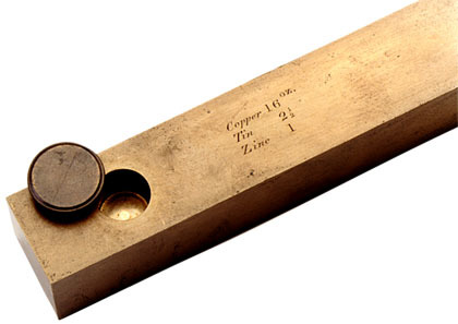 End of a bronze-colored ruler used to measure the survey foot