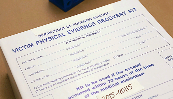 A white cardboard box with blue lettering contains a sexual assault kit.